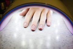 Frauenhand innerhalb der Lampe für Nägel auf Tabellenabschluß oben UVlampe für Lizenzfreie Stockbilder