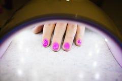 Frauenhand innerhalb der UVlampe für Nägel auf Tabelle stockbilder