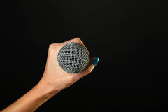Frauenhand mit dem Mikrofon lokalisiert auf Schwarzem Lizenzfreie Stockbilder