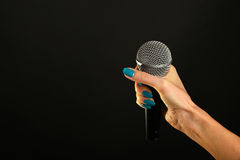 Frauenhand mit dem Mikrofon lokalisiert auf Schwarzem Stockbild