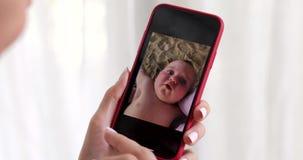 Frauenhand mit dem Smartphone, der Kinderbild zeigt stock video footage