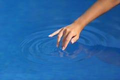 Frauenhand mit der perfekten Maniküre, die mit Wasser in einem Pool spielt lizenzfreies stockbild