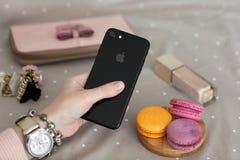 Frauenhand mit der Uhr, die iPhone 7 Jet Black Onyx hält Lizenzfreie Stockfotos