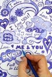 Frauenhand mit Kugelschreiber zeichnet Liebesgekritzelmitteilungen Stockfotos
