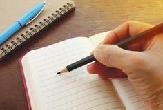 Frauenhand mit schwarzem Bleistiftschreiben auf leerem Notizbuch auf Holztisch Stockfoto
