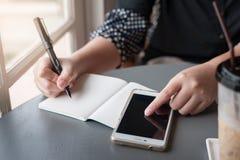 Frauenhand mit Stiftschreiben auf Notizblock Stockbilder