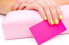 Frauenhand mit Visitenkarte für Schönheitssalon Lizenzfreies Stockbild