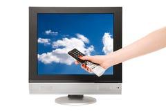 Frauenhand und Fernsehbildschirm mit blauem Himmel Stockbilder