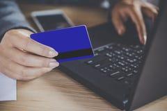 Frauenhand unter Verwendung der Kreditkarte und Schreiben auf Computernotizbuch für online kaufen Lizenzfreie Stockbilder