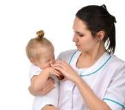 Frauenhand unter Verwendung des Medizinnasensprays nasal für Babykleinkind Stockfotografie