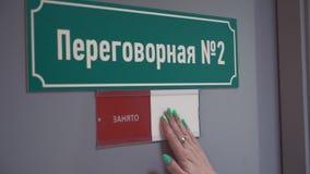 Frauenhand verschiebt Platte auf besetzt auf Tür mit kyrillischem TextKonferenzzimmer stock footage