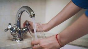 Frauenhanddrehengriff auf Hahn und strömendem Wasser in Glas stock video footage
