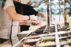 Frauenhandgabel vorbei für Abendessensalat stockfotos