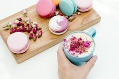 Frauenhandgriff-Cappuccinoschale mit den Rosenblumenblättern Schönheit französische macarons auf hölzernem Schreibtisch und weiße Stockfotografie