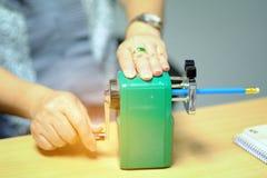 Frauenhandgriff, den der grüne sharping Bleistiftspitzer auf offi zensieren Stockfotos