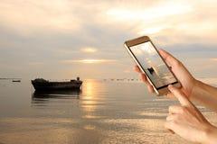 Frauenhandgriff- und -touch Screen intelligentes Telefon über schönem Meer und altes Boot in PATTAYA, Thailand am Abend stockfotografie