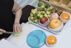 Frauenhandgriffmesser-Ausschnittvielzahl von Fruchtkiwi-Traubenäpfeln stockfoto