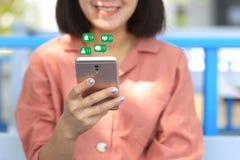 Frauenhandholding Smartphone für die Prüfung des Social Media mit Ikone oder Hologramm in der Kaffeestube, Kommunikationsnetzinte stockfotografie