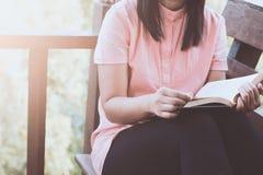 Frauenhandholding und -lesung ein Buch auf dem Stuhl am Haus lizenzfreies stockbild