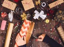 Frauenhandholdingrolle von Kraftpapier-Packpapier mit Scheren für den Schnitt der Verpackungsweihnachtsgeschenkbox lizenzfreie stockfotos