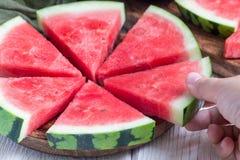 Frauenhandnehmenscheibe der frischen samenlosen Wassermelone schnitt in Dreieck die Form, die auf eine hölzerne Platte legt, hori Lizenzfreies Stockfoto