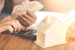 Frauenhandrechengeld mit Hausmodell auf dem Holztisch, der planiert, um nach Hause zu kaufen oder zu mieten lizenzfreies stockfoto