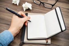 Frauenhandschreiben auf Notizbuch Stockfoto
