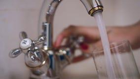 Frauenhandströmendes Wasser in Glas vom Wasserhahn auf Küche stock video
