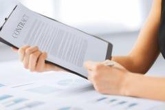 Frauenhandunterzeichnendes Vertragspapier stockbilder