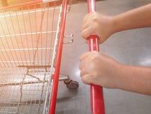 Frauenhandwagenhalter im Supermarkt lizenzfreie stockfotos
