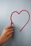 Frauenhandzeichnungsherz für Valentinsgrußtag mit roter Kreide auf w Lizenzfreies Stockfoto