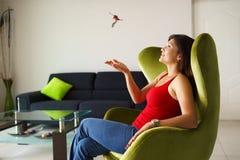 Frauenhauseigentümer, der mit Schlüsseln des neuen Hauses auf Sofa spielt Lizenzfreies Stockbild