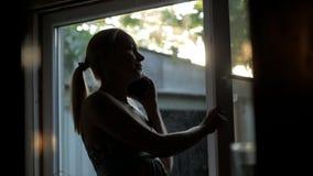 Frauenhausfraustellung am Fenster in seinem Haus, das am Telefon spricht stock video