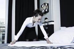 Frauenhaushälterin, die Bett in einem Hotelschlafzimmer tut Stockfotografie