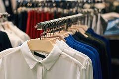 Frauenhemden amd Blusen in den wei?en, blauen, schwarzen und anderen Farben auf Aufh?ngern in einem Kleinkleidungsspeicher lizenzfreie stockbilder