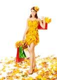 Frauenherbsteinkaufen im Kleid von Ahornblättern über Weiß Lizenzfreies Stockfoto