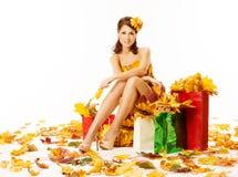 Frauenherbsteinkaufen im Kleid von Ahornblättern über Weiß Stockfotos