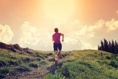 Frauenhinterläufer, der auf schöner Bergspitze läuft Stockfotografie