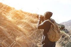 Frauenhippiephotograph mit dslr Kamera machen Fotos Stilvolles Mädchen in der Sonnenbrille mit einer Kamera auf der Natur Stockfoto