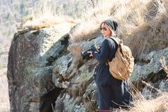 Frauenhippiephotograph mit dslr Kamera Stilvolles Mädchen in der Sonnenbrille mit einer Kamera auf der Natur Stockbild