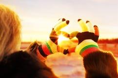 Frauenhände in den Winterhandschuhen hintergrundbeleuchtet durch die Herzenswärme der Sonne Lizenzfreie Stockfotos
