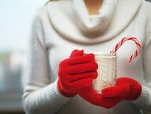 Frauenhände in den woolen roten Handschuhen, die einen gemütlichen Becher mit heißem Kakao, Tee oder Kaffee und eine Zuckerstange Stockfotos