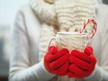 Frauenhände in den woolen roten Handschuhen, die einen gemütlichen Becher mit heißem Kakao, Tee oder Kaffee und eine Zuckerstange Lizenzfreie Stockfotografie