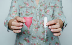 Frauenhände, die Menstruationsschale mit einem Tampon vergleichen Stockfotografie