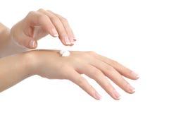 Frauenhände mit der perfekten Maniküre, die Feuchtigkeitscremecreme aufträgt Stockfotos