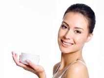 Frauenholding, die Gesichtssahne befeuchtet Stockfoto