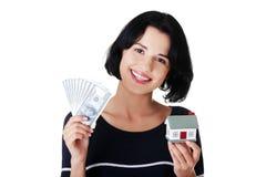 Frauenholding Dollarrechnungen und -haus formen stockbild