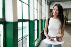 Frauenholding gefror Kaffee und das Schauen aus Fenster heraus Stockfoto