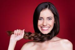 Frauenholding ihre Flechte und Lächeln Stockfoto