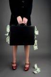 Frauenholdingaktenkoffer, der mit Geld überläuft Stockbild